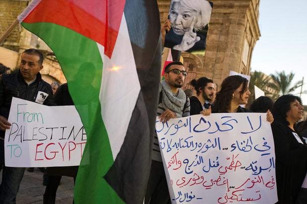 Photo : des citoyens palestiniens d'Israël brandissent une photo de la féministe égyptienne et romancière de premier plan Nawal el-Saadawi lors d'une manifestation contre les violences sexuelles faites aux femmes en Égypte, à Jaffa, au nord de Tel-Aviv, le 12 février 2013 (AFP).