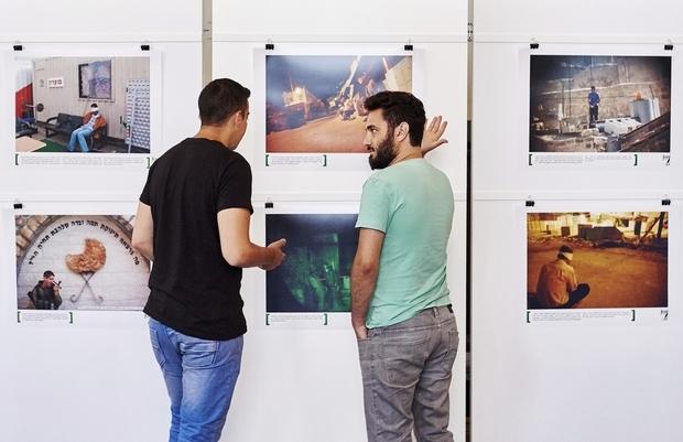 Alon Sahar (à gauche) et Shay Davidovich, deux anciens soldats de l'armée israélienne, discutent en regardant les photographies d'une exposition organisée par l'ONG Breaking the Silence le 3 juin 2015 à la Kulturhaus Helferei de Zurich, en Suisse (AFP)